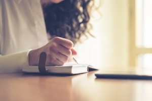 Woman-journaling-writing-pen-notebook